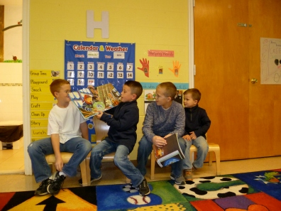 Three alumni boys return to read to their youngest brother's class.